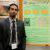Brandon D'Souza stands next to his research poster.